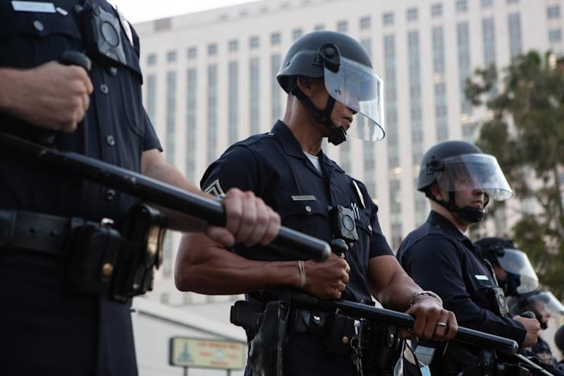 LOS ANGELES, CA - MAY 27: Los Angeles Police Department officers form a police line in riot gear after a Black Lives Matter Protest in solidarity with other national demonstrations to show outrage over the death of George Floyd in downtown Los Angeles on Wednesday, May 27, 2020 in Los Angeles, CA. (Gabriella Angotti-Jones / Los Angeles Times)