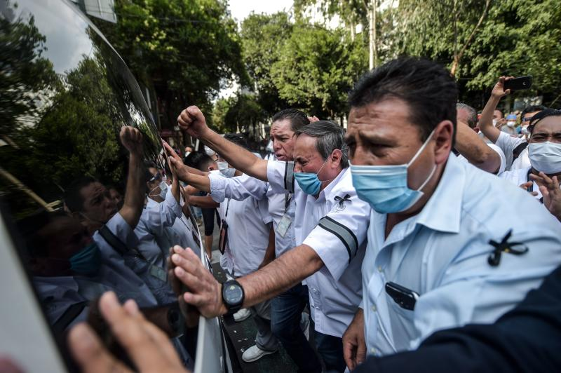 "TOPSHOT - Health workers of ""20 de Noviembre"" hospital farewell his fellow stretcher-bearer Hugo Lopez Camacho, who died of Covid-19, in Mexico City, on May 18, 2020. - The novel coronavirus has killed more than 30,000 people in Latin America and the Caribbean since the outbreak first emerged in China last December, according to the latest tally from official sources compiled by AFP on Monday. (Photo by PEDRO PARDO / AFP) (Photo by PEDRO PARDO/AFP via Getty Images)"