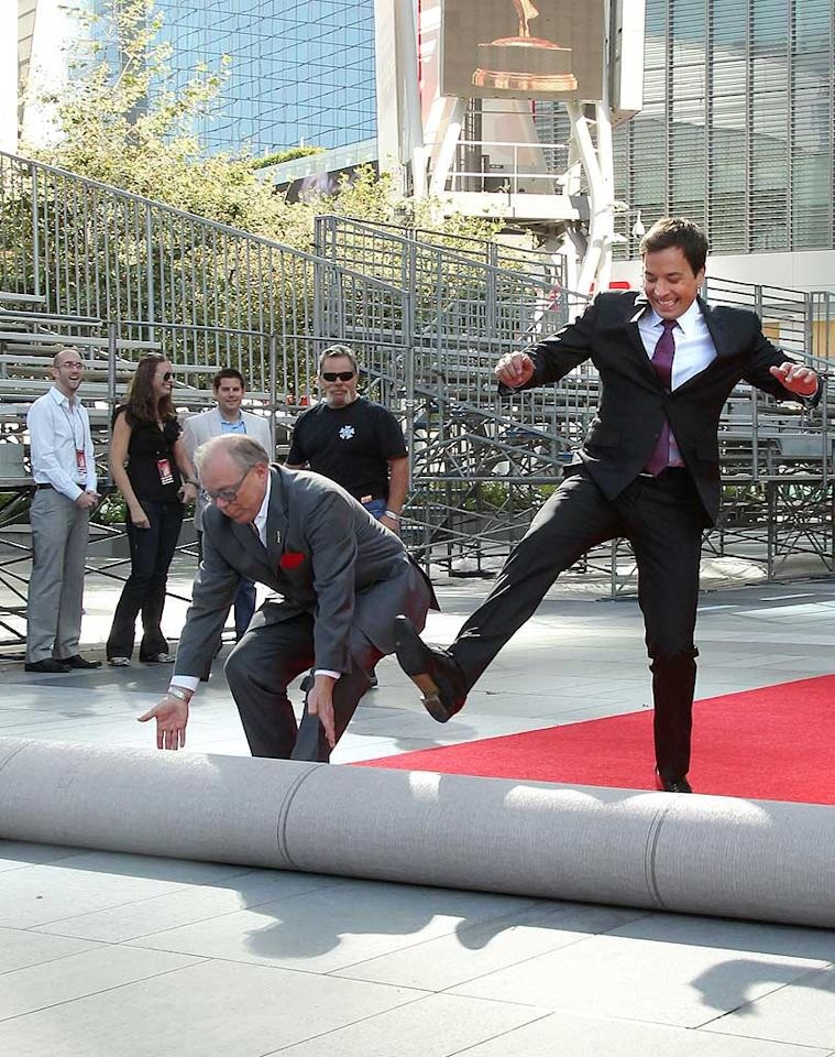 """Hello Emmys! The host of the annual TV awards show, Jimmy Fallon, rolled out the red carpet in preparation for the procession of glamorous gowns that will grace it Sunday night. Who knew manual labor was part of the host's job description?! Mathew Imaging/<a href=""""http://www.wireimage.com"""" target=""""new"""">WireImage.com</a> - August 25, 2010"""