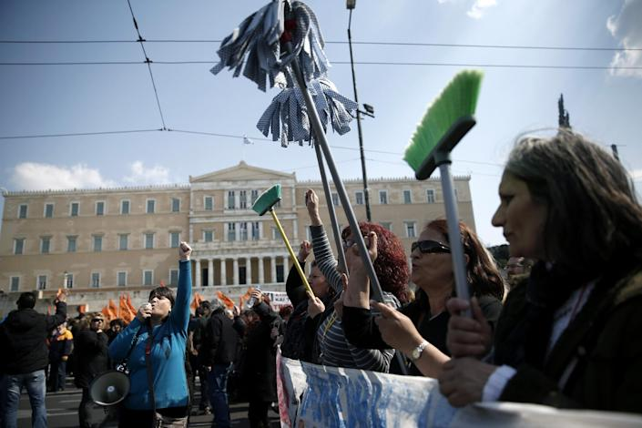 Protesting cleaning staff fired by the Finance Ministry marched holding up buckets and mops during a rally outside the Greek parliament in central Athens on Wednesday, March 12, 2014. A 24-hour strike by civil servants disrupted public services in Greece Wednesday as the country's government struggled to hammer out a deal on further austerity measures with international creditors. Thousands of protesters attended rallies in Athens and other Greek cities, while civil servants have penciled in another 48-hour strike on March 19-20. (AP Photo/Petros Giannakouris)