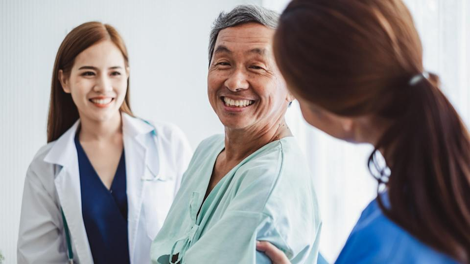 Asian doctor woman and nurse encourage disabled old man patient sitting on wheelchair at hospital, asian medical concept.