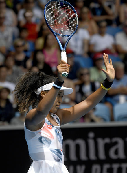 In this Jan. 22, 2020 photo, Japan's Naomi Osaka gestures to her opponent China's Saisai Zheng after her shot hit the net during their second round match at the Australian Open tennis championship in Melbourne, Australia. It might just be the most insincere gesture in sports: A tennis player signals an apology after a ball clips the net tape and trickles over, producing a winner, an obviously accidental winner, to end a point. (AP Photo/Andy Brownbill)