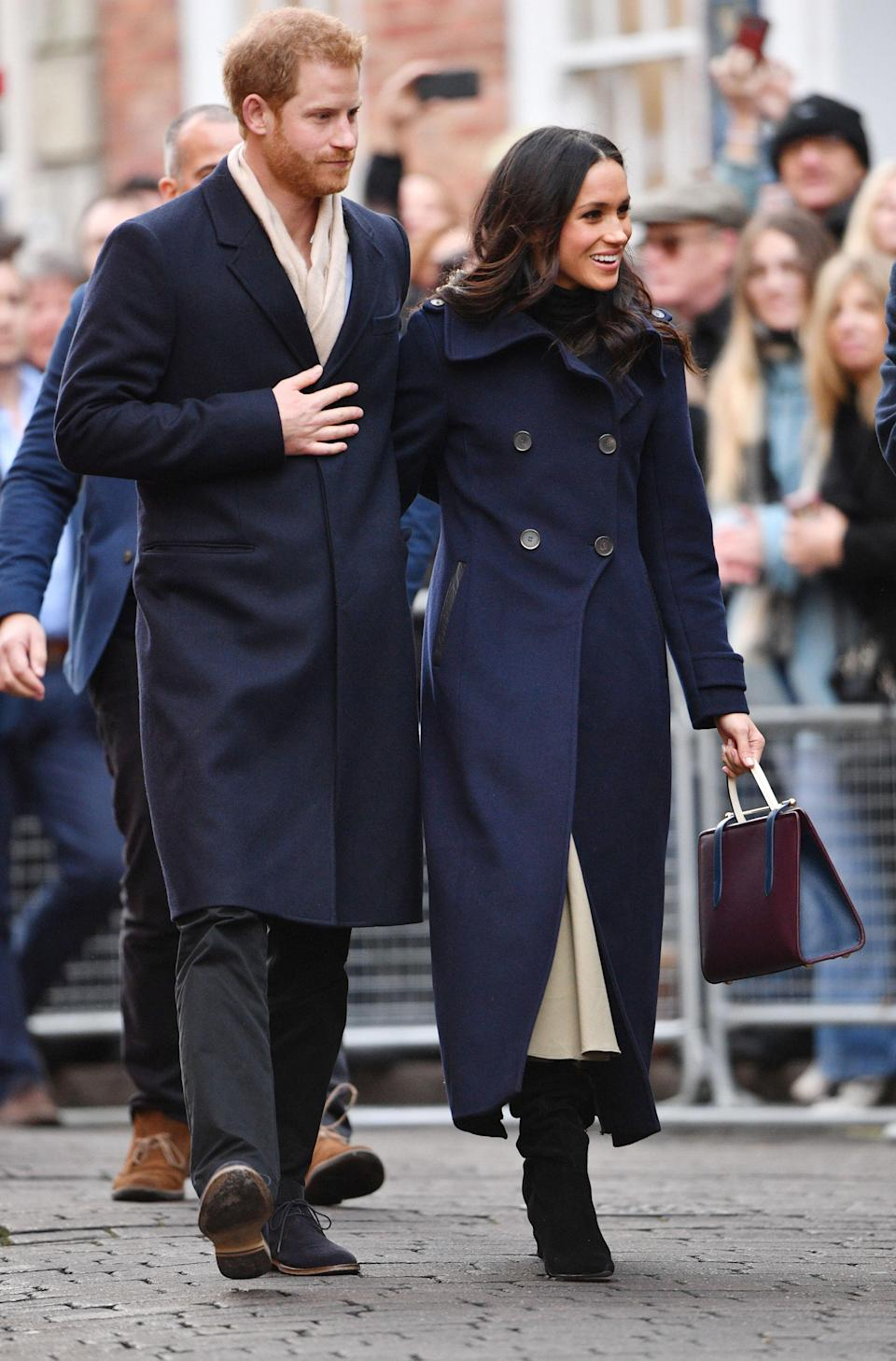 <p>Meghan began royal life with a trip to Nottingham. For her first meeting with the British public, the 36-year-old donned a navy double-breasted coat by Canadian label Mackage, a turtleneck Wolford, cream Joseph skirt and heeled suede boots. She carried a burgundy leather handbag; something the Duchess of Cambridge rarely does. <i>[Photo: Rex]</i> </p>