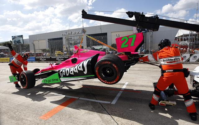 The car driven by James Hinchcliffe, of Canada, is towed away after crashing during the first IndyCar Grand Prix of Houston auto race, Saturday, Oct. 5, 2013, in Houston. (AP Photo/Patric Schneider)