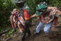 An Indonesian soldier assists a woman to carry her baby as they make their way through an area affected by earthquake-triggered landslide near Mamuju, West Sulawesi, Indonesia, Saturday, Jan. 16, 2021. Damaged roads and bridges, power blackouts and lack of heavy equipment on Saturday hampered Indonesia's rescuers after a strong and shallow earthquake left a number of people dead and injured on Sulawesi island. (AP Photo/Yusuf Wahil)