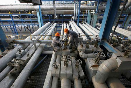 FILE PHOTO: Employees close a valve of a pipe at a PetroChina refinery in Lanzhou, Gansu province