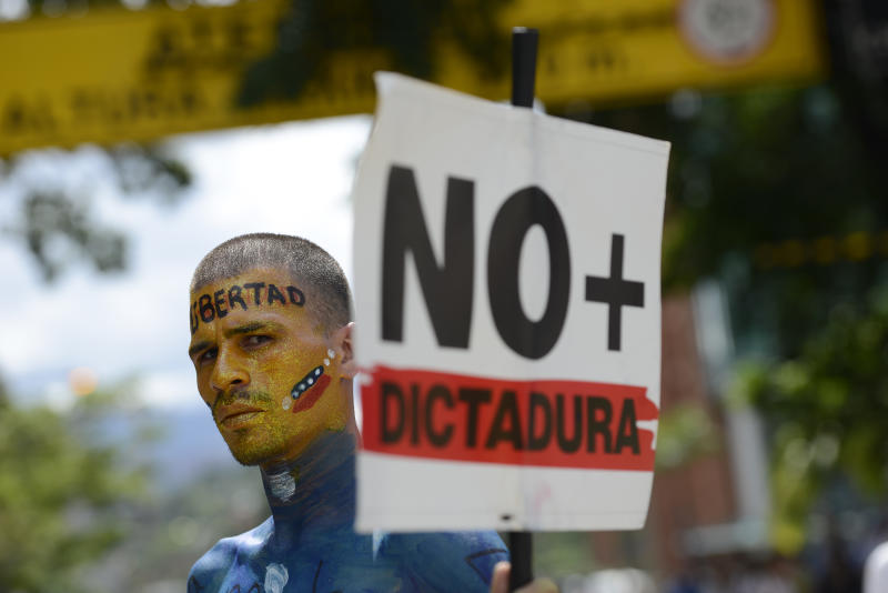 "A man holding a sign with a message that reads in Spanish: ""No more dictatorship,"" takes part in a demonstration led by opposition politician Juan Guaido, who's urging masses into the streets to force President Nicolas Maduro from power, in Caracas, Venezuela, Saturday, Nov. 16, 2019.  Guaido called nationwide demonstrations to re-ignite a campaign against Maduro launched in January that has lost steam in recent months. (AP Photo/Matias Delacroix)"