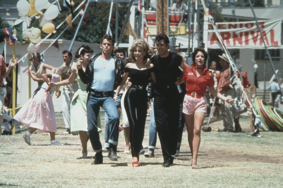 1978:  Left to right: actors Jeff Conaway, Olivia Newton-John, John Travolta and Stockard Channing walk arm in arm at a carnival in a still from the film, 'Grease' directed by Randal Kleiser.  (Photo by Paramount Pictures/Fotos International/Getty Images)