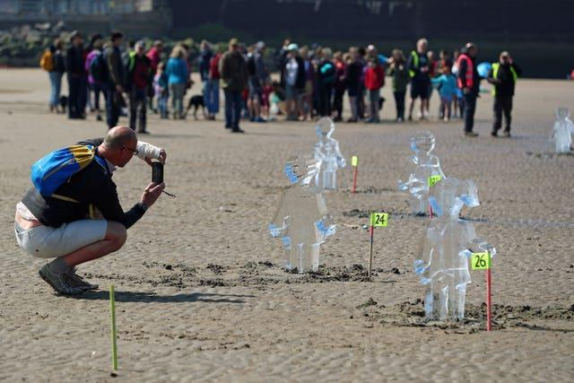 Members of the public look at some of 26 ice sculptures of children installed on New Brighton Beach, Wallasey in Merseyside