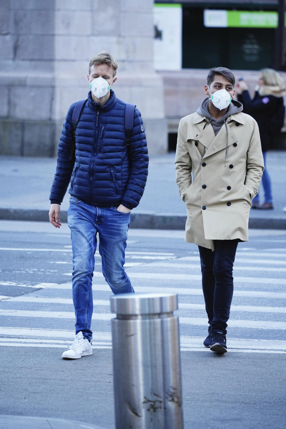 Photo shows two men walking across a street wearing face masks.