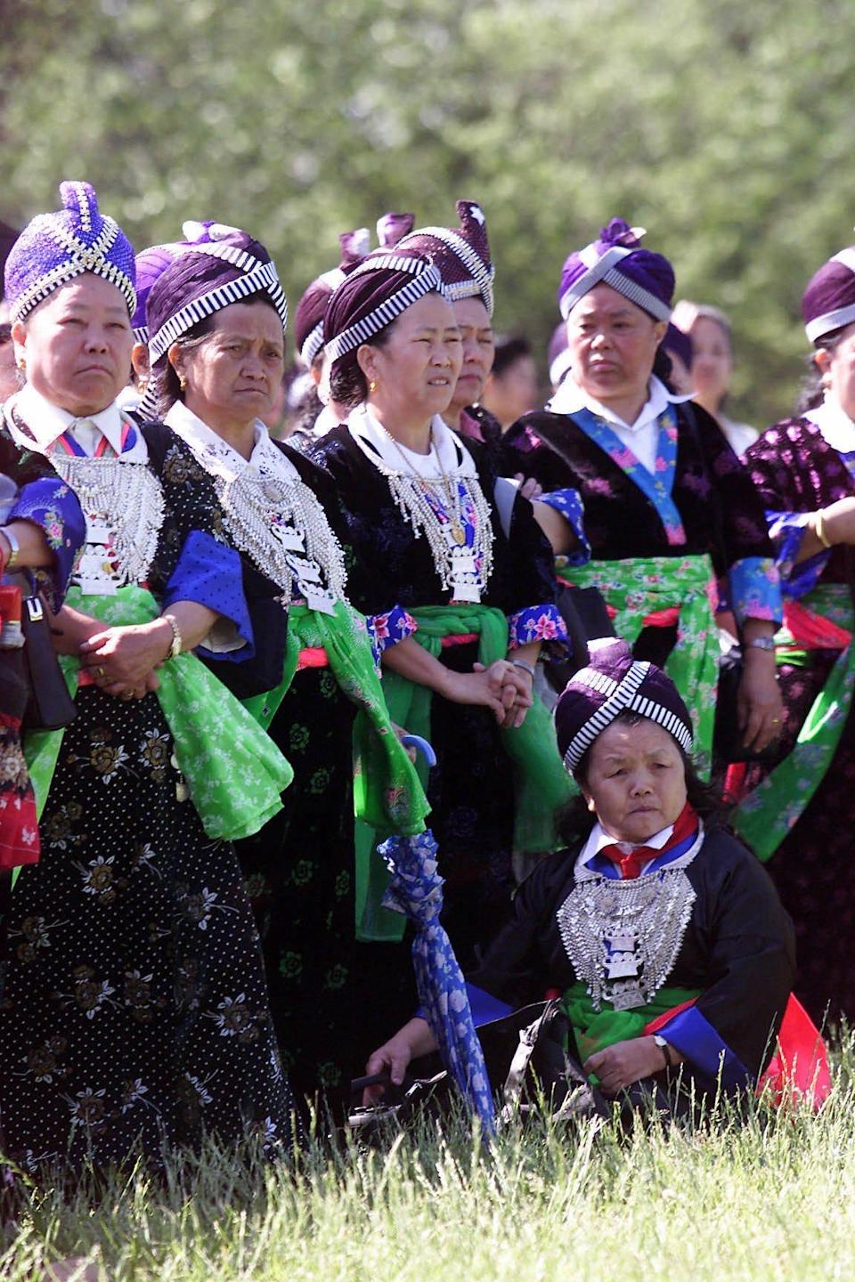 Hmong women wearing formal dresses used for special events, watching as Hmong and other Laotian-born vietnam veterans march to the Vietnam Veterans Memorial to mark the 25th anniversary of the end of the Vietnam War, Thursday morning in Washington, D.C. The color of the dresses indicate the village from which they come. (GNS Photo by Heather Martin Morrissey)