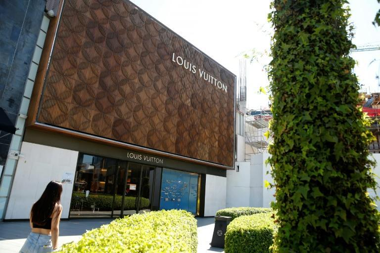 A woman walks past a luxury store at Las Condes commune in Santiago on October 31, 2020