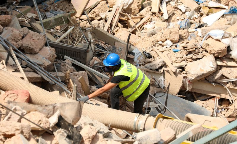 FILE PHOTO: A volunteer digs through the rubble of buildings which collapsed due to the explosion at the port area, after signs of life were detected, in Gemmayze, Beirut