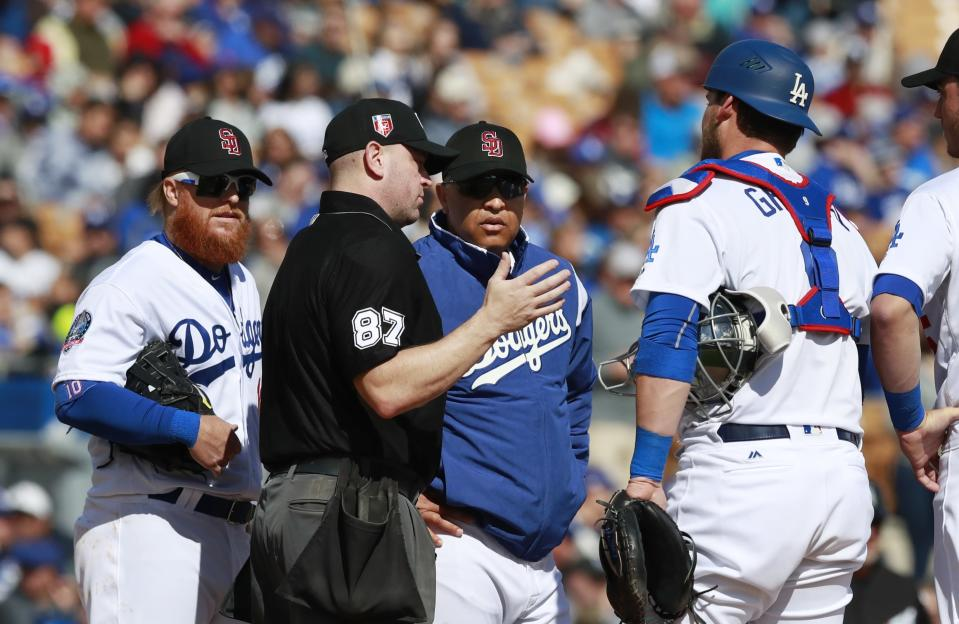 Home plate umpire Scott Barry talks with Los Angeles Dodgers manager Dave Roberts during a mound visit in the Dodgers' baseball spring training game against the Chicago White Sox. (AP Photo/Carlos Osorio)