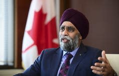 Harjit Sajjan, wearing a turban and suit and tie, gestures as he speaks.