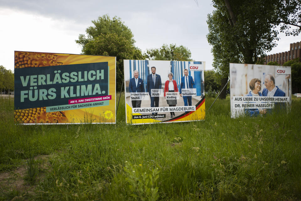 """Election campaign posters from the Greens and Merkel's Christian Democratic Union party stand near a road in the federal state Saxony-Anhalt's capital Magdeburg, Germany, Wednesday, June 2, 2021. The state vote on Sunday, June 6, 2021 is German politicians' last major test at the ballot box before the national election in September that will determine who succeeds Chancellor Angela Merkel. The from left: A poster of the Green Party with the slogan: reliable for climate reliable for Saxony-Anhalt, center a poster of the CDU showing candidates and reading; """"together for Magdeburg' and right a poster showing ruling CDU governor Reiner Haseloff with bis wife Gabriele Haseloff and the slogan: Out of love for our homeland'. (AP Photo/Markus Schreiber)"""