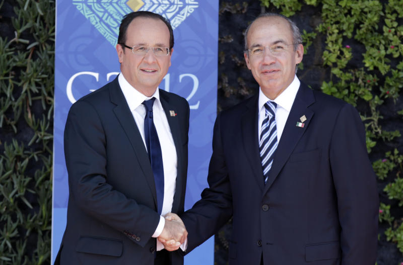France's President Francois Hollande, left, shakes hands with Mexico's President Felipe Calderon as they pose for pictures during the opening ceremony of the G20 Summit in Los Cabos, Mexico, Monday, June 18, 2012. (AP Photo/Eduardo Verdugo)