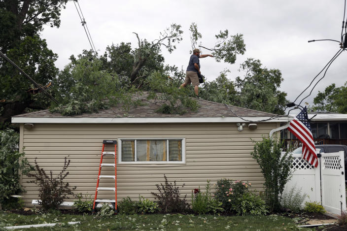 A Woodridge, Ill., homeowner clears the damaged trees off his house after a tornado passed through the area on Monday, June 21, 2021. (AP Photo/Shafkat Anowar)