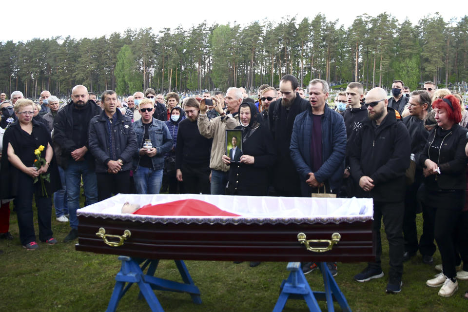 Relatives and friends of Vitold Ashurok stand at the coffin with his body draped with white and red cloth in the color of Old Berurian national flag in Minsk, Belarus, Wednesday, May 26, 2021. One of those who first reported cruel conditions and yellow tags for political prisoners, the 50-year-old Vitold Ashurok, suddenly died in prison in Shklov where he was serving a five-year sentence for taking part in protests. The authorities said Ashurok died of a heart attack on May 21, although the official death certificate didn't list the cause of death. Political prisoners in Belarus are coming under increasing pressure following the recent arrest of activist Raman Pratasevich from a forcibly diverted Ryanair flight. (AP Photo)