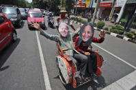 Indonesian men wearing masks of President-elect Joe Biden and Vice President-elect Kamala Harris wave as they sit on a tricycle as they celebrate their win in the U.S. presidential election, in Solo, Centra Java, Indonesia, , Sunday, Nov. 8, 2020. (AP Photo)