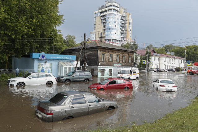 Cars sit in flood water after a heavy rain in Nizhny Novgorod, Russia, Tuesday, June 19, 2018. Nizhny Novgorod Stadium is hosting six matches during the Russia 2018 World Cup. (AP Photo/Pavel Golovkin)