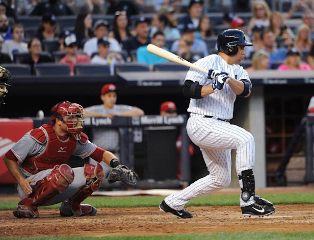 New York Yankees designated hitter Carlos Beltran follows through on an RBI single off Cincinnati Reds starting pitcher Mike Leake as Devin Mesoraco catches for the Reds in the third inning of an interleague baseball game at Yankee Stadium on Friday, July 18, 2014, in New York. (AP Photo/Kathy Kmonicek)