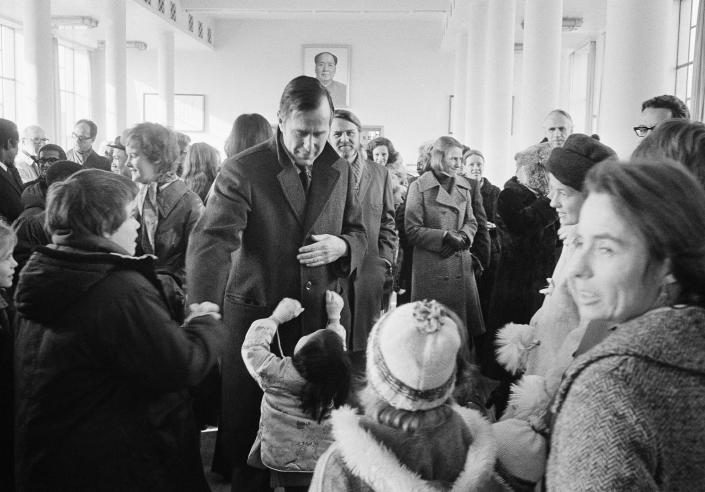<p>U.S. Chief of Mission George Bush greets family members of the U.S. Liaison Mission on Dec. 7, 1975, in the lounge at Peking International Airport as he gets ready to depart for Washington, after being nominated to head the Central Intelligence Agency. (Photo: AP) </p>