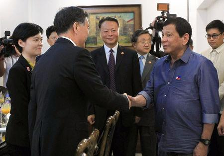 Philippine President Rodrigo Duterte greets Vice Premier of China, Wang Yang (L) during his courtesy call at the Presidential Guest House in Davao city