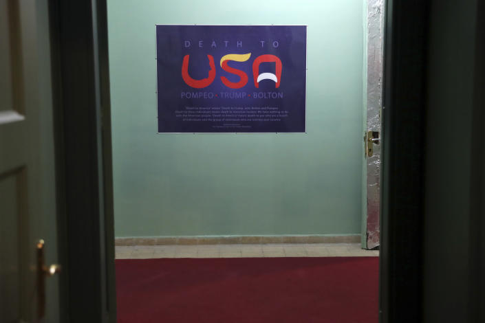 """In this Sept. 26, 2019, photo, an anti-U.S. placard adorns a corridor of the former U.S. Embassy in Tehran, now partly a museum, Iran. The slogan in English reads: """"Death to the USA,"""" with the letter """"U"""" bearing the profile of U.S. Secretary of State Mike Pompeo; the """"S"""" the pompadour of President Donald Trump; and the """"A"""" the mustache of former U.S. national security adviser John Bolton, a longtime hawk on Iran. (AP Photo/Vahid Salemi)"""