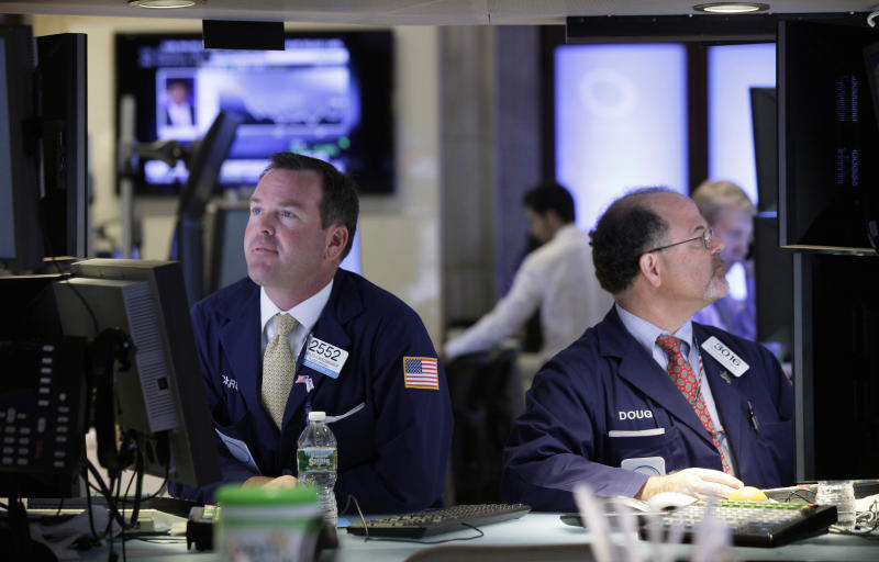 FILE- In this Tuesday, July 17, 2012, file photo, Specialists Charles Boeddinghaus, left, and Douglas Johnson, work at their posts on the floor of the New York Stock Exchange Tuesday, July 17, 2012. Renewed hope for more help from the Fed supported markets, as did positive earnings statements from Goldman Sachs, Coca Cola and Yahoo. U.S. earnings statements will remain a focus of attention later.  (AP Photo/Richard Drew, File)