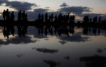 FILE PHOTO: Palestinian demonstrators are reflected in rain water after attending a protest calling for lifting the blockade on Gaza, at the Israel-Gaza border fence in Gaza October 26, 2018. REUTERS/Mohammed Salem/File Photo