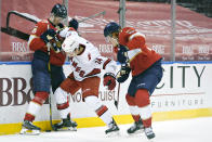 Florida Panthers center Eetu Luostarinen (27) and right wing Owen Tippett, right, battle for the puck with Carolina Hurricanes defenseman Jake Bean (24) during the second period of an NHL hockey game, Monday, March 1, 2021, in Sunrise, Fla. (AP Photo/Wilfredo Lee)