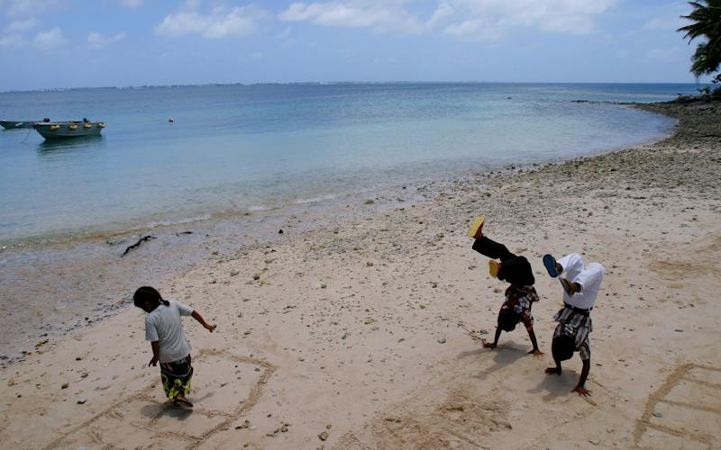 Bikinian children play on the beach of Ejit island, after Palm Sunday church service, in the Marshall Islands, April 4, 2004. (AP Photo/Richard Vogel)