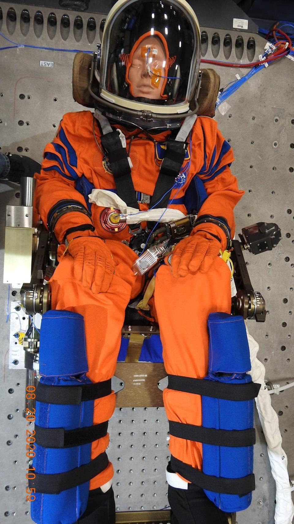 A dummy in an orange space suit sitting in a chair