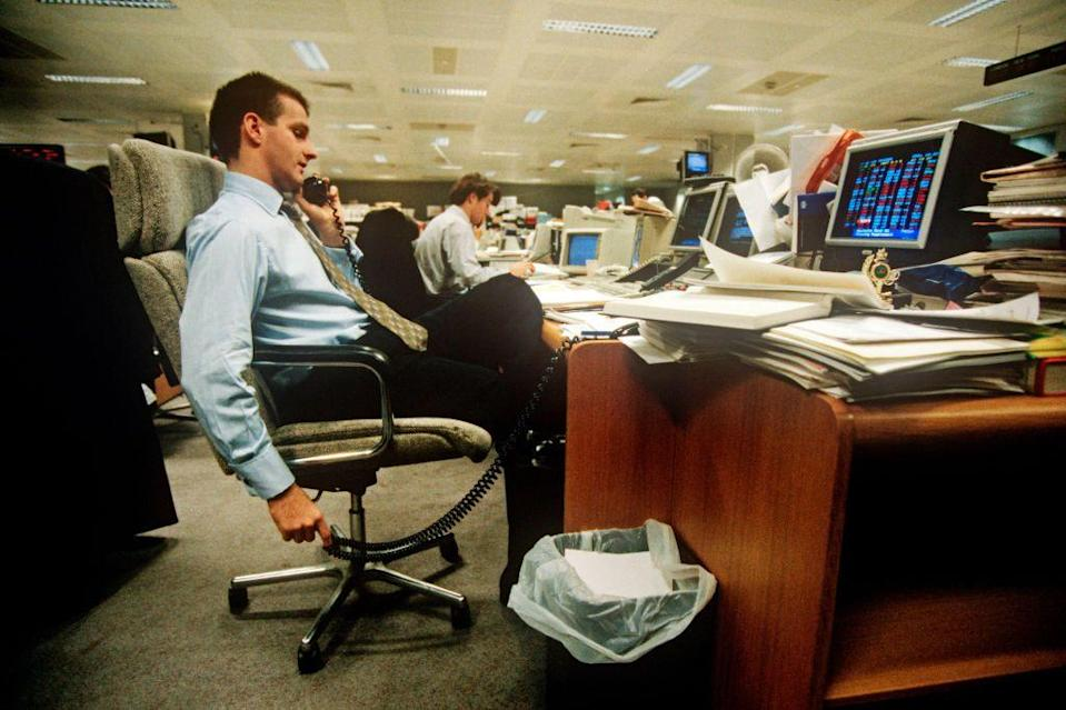 <p>A banker working on the trading floor takes a call at his desk in a set-up that looks pretty familiar to present-day office life. The financial sector relies on technology and the rise of computing to manage day-to-day tasks such as compiling financial data, organizing the data in charts and graphs, and running complex transactions.</p>