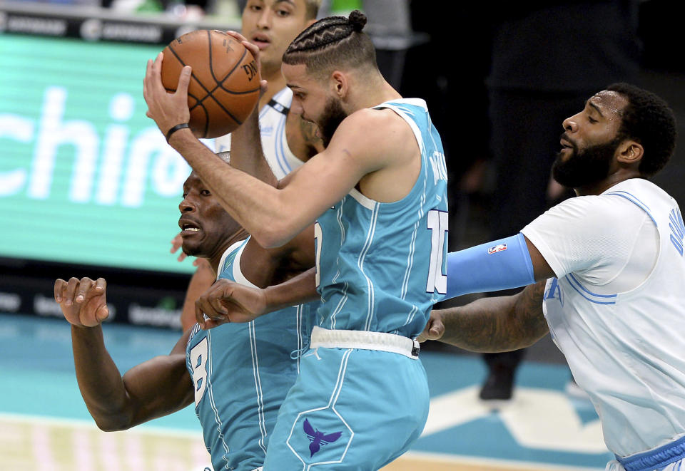 Charlotte Hornets forward Caleb Martin, center, grabs control of a rebound with teammate and center Bismack Biyombo, left, as Los Angeles Lakers center Andre Drummond, right, looks on during the first half of an NBA basketball game in Charlotte, N.C., Tuesday, April 13, 2021. (Jeff Siner/The Charlotte Observer via AP)