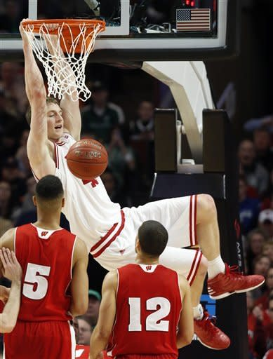 Wisconsin's Ryan Evans (5) and Traevon Jackson (12) watch as Indiana's Cody Zeller dunks during the second half of an NCAA college basketball game at the Big Ten tournament Saturday, March 16, 2013, in Chicago. (AP Photo/Charles Rex Arbogast)