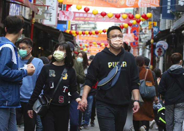 In this Wednesday, Feb. 10, 2021, file photo, visitors wearing face masks to help curb the spread of the coronavirus the famed shopping area of Dihua Street market in Taipei, Taiwan, Wednesday, Feb 10, 2021. Taiwan says it will begin slightly easing restrictions on foreign visitors coming to the island beginning Monday. (AP Photo/Chiang Ying-ying, File)