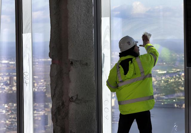 A Port Authority worker cleans a window of the unfinished observation deck on the 100th floor of the One World Trade Center building, under construction in New York, Tuesday, April 2, 2013. The observation deck will occupy the tower's 100th through 102nd floors. Elevators will whisk visitors to the top in just one minute but the experience of visiting the attraction will take an hour. (AP Photo/Richard Drew)