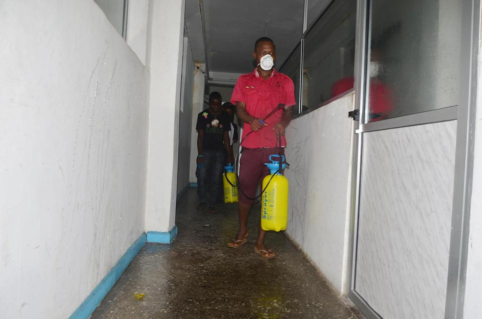 An employee disinfects an office in Monrovia closed for disinfection against the Ebola epidemic, August 1, 2014 (AFP Photo/Zoom Dosso)