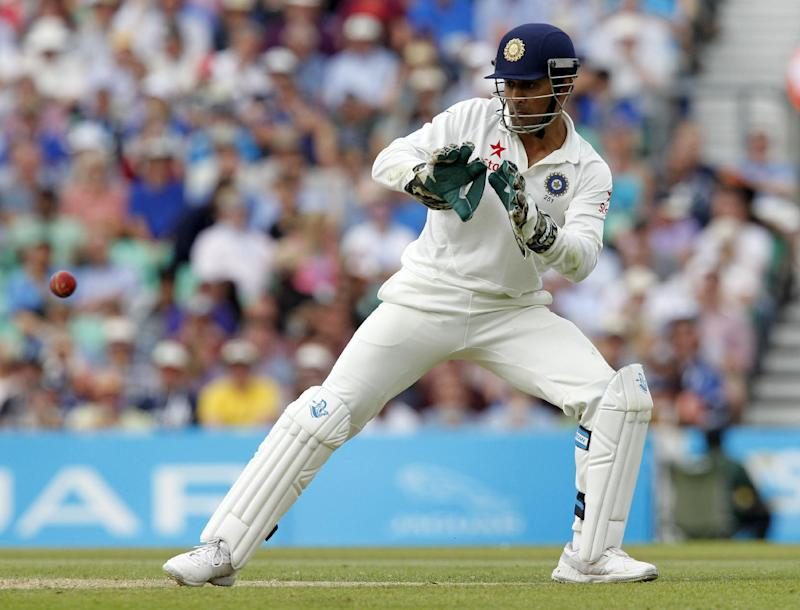 India's captain and wicketkeeper Mahendra Singh Dhoni fields the ball on the second day of the fifth cricket Test match between England and India at The Oval in London on August 16, 2014