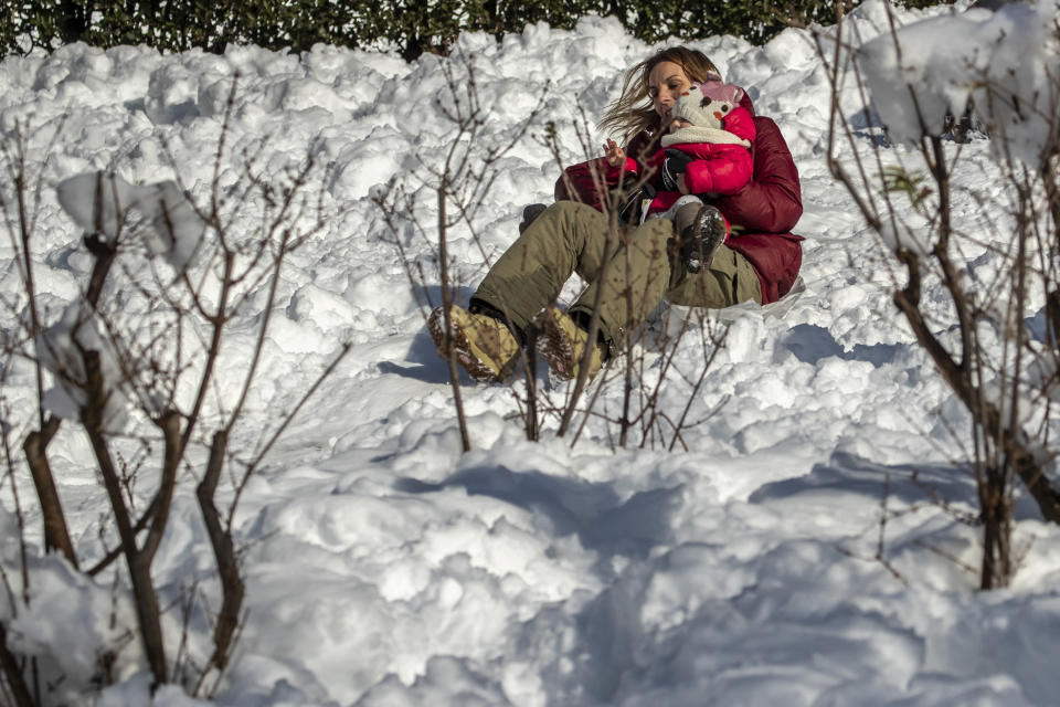 A woman child enjoy the snow in downtown Madrid, Spain, Sunday, Jan. 10, 2021. A large part of central Spain including the capital of Madrid are slowly clearing snow after the country's worst snowstorm in recent memory. (AP Photo/Manu Fernandez)