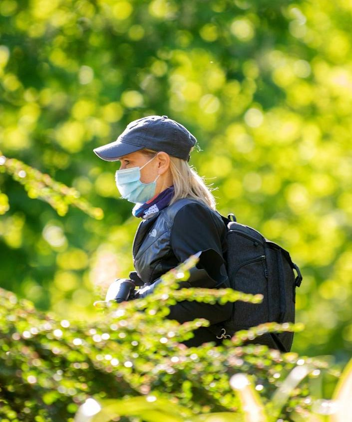 NEW YORK, NEW YORK – MAY 13: A woman wearing a mask carries a camera in Central Park amid the coronavirus pandemic on May 13, 2020 in New York City. COVID-19 has spread to most countries around the world, claiming over 297,000 lives with over 4.4 million cases. (Photo by Alexi Rosenfeld/Getty Images)