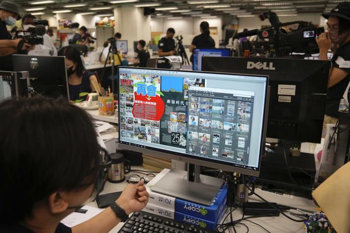 Staff members design their layout for the last edition of newspaper in the Apple Daily headquarters in Hong Kong, Wednesday, June 23, 2021. Hong Kong's pro-democracy Apple Daily newspaper will stop publishing Thursday, following last week's arrest of five editors and executives and the freezing of $2.3 million in assets under the city's year-old national security law. (AP Photo/Kin Cheung)