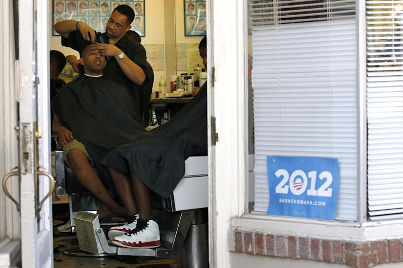 """Dorsey Jackson cuts Be-Emnet Zegeye's hair at his establishment Jackson's Barbershop, Friday, May 11, 2012, in Ardmore, Pa. Like many black Americans, Dorsey Jackson does not believe in gay marriage, but he wasn't disillusioned when Barack Obama became the first president to support it. The windows of his suburban Philadelphia barbershop still display an """"Obama 2012"""" placard and another that reads """"We've Got His Back."""" (AP Photo/Matt Rourke)"""