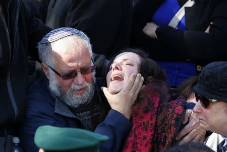 A family member mourns during the funeral for Captain Yochai Kalangel at Mount Herzl military cemetery in Jerusalem January 29, 2015.  REUTERS/Ronen Zvulun