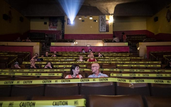 Attendees wait for the start of a movie at the Mayfair Theatre on its first day of reopening, in Ottawa, Ontario, Canada - Justin Tang/Bloomberg