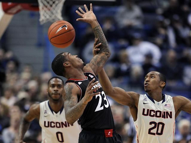 Cincinnati's Sean Kilpatrick (23) and Connecticut's Lasan Kromah (20) fight for a loose ball during the first half of an NCAA college basketball game in Hartford, Conn., Sunday, March 1, 2014. (AP Photo/Fred Beckham)
