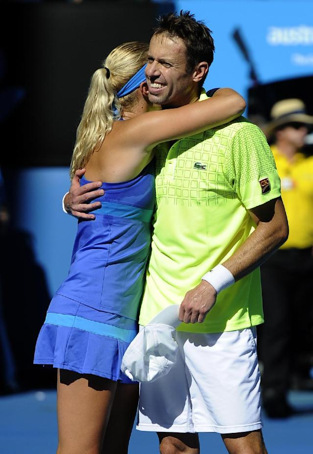 Kristina Mladenovic of France and Daniel Nestor of Canada celebrate after defeating Sania Mirza of India and Horia Tecau of Romania in their mixed doubles final at the Australian Open tennis championship in Melbourne, Australia, Sunday, Jan. 26, 2014.(AP Photo/Andrew Brownbill)