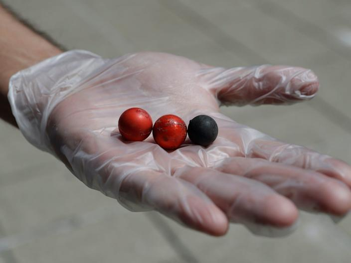 A volunteer holds pepper balls in his hand that was collected with other debris as he cleaned after a night of protests in downtown Louisville, Kentucky, on Sunday.